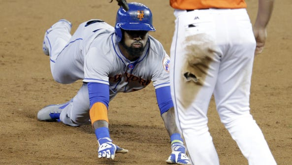 The Mets' Jose Reyes slides into third base with an