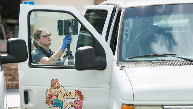 An Escambia County Sheriff Office crime scene investigator sets up a FARO laser scanner outside a day care van while investigating the death of a child at the In His Arms Christian Academy in Pensacola on Friday, August 18, 2017.