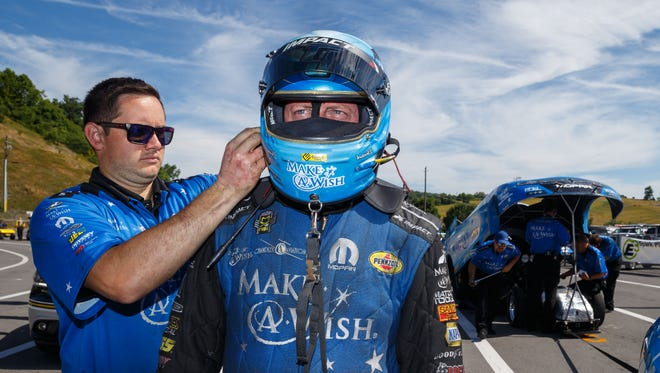 A crew member helps NHRA funny car driver Tommy Johnson Jr. put on safety gear during the Thunder Valley Nationals at Bristol Dragway.
