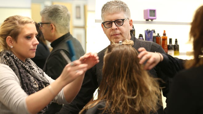 Scott Miller looks on as styling apprentice Sierra Thompson works on a client's hair at his Scott Miller salon in Pittsford.