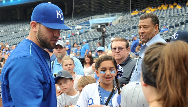 Kansas City Royals third baseman Mike Moustakas signs autographs for young fans before a game against the Cleveland Indians.
