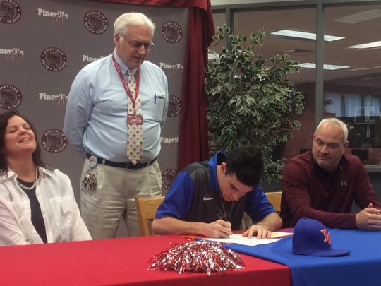 Pineville senior shortstop Tyler Atkins signs to play for the Louisiana College baseball team Tuesday afternoon as his parents, Kelly (left) and Joel Atkins (right), and Pineville High School Principal Karl Carpenter (standing) look on.