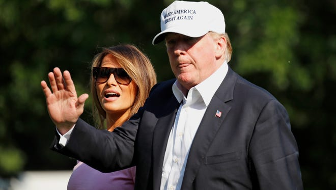 President Donald Trump waves after stepping off Marine One, accompanied by first lady Melania Trump, on the South Lawn of the White House, Sunday, July 1, 2018, in Washington.