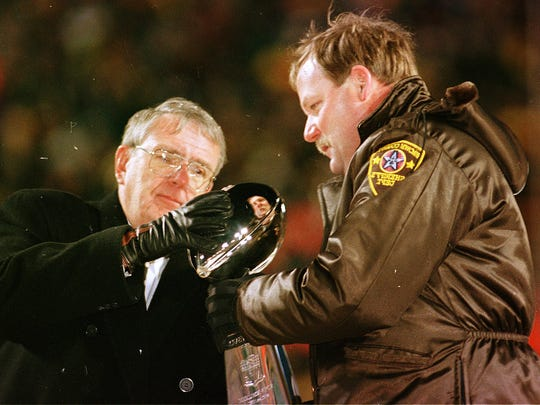 General manager Ron Wolf and coach Mike Holmgren celebrate the Super Bowl XXXI win at Lambeau Field.  Holmgren was loaned a sheriff deputy's jacket because he had no heavy coat for the chilly parade through Green Bay.