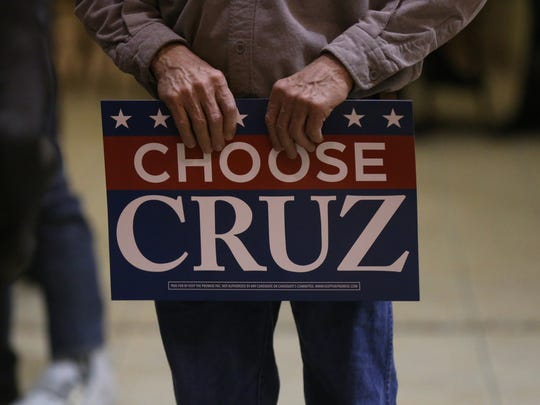 """A man holds a """"Choose Cruz"""" campaign poster during a campaign stop for presidential hopeful Ted Cruz in Fairfield at about 7:45 p.m. Tuesday, Jan. 26, 2016."""