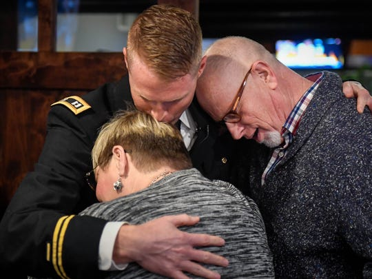 Rick and Judy Chandler embrace their son Army Reserve Chaplain Owen R. Chandler at a surprise party where they saw Owen for the first time since he started a military tour in Iraq Wednesday, February 22, 2017.