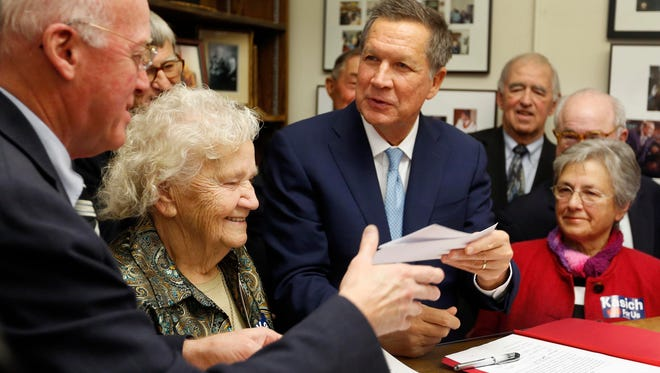 Republican presidential candidate, Ohio Gov. John Kasich hands over his filing fee to New Hampshire Secretary of State Bill Gardner while filing papers to be on the nation's earliest presidential primary ballot, Friday, at The Secretary of State's offic in Concord, N.H.