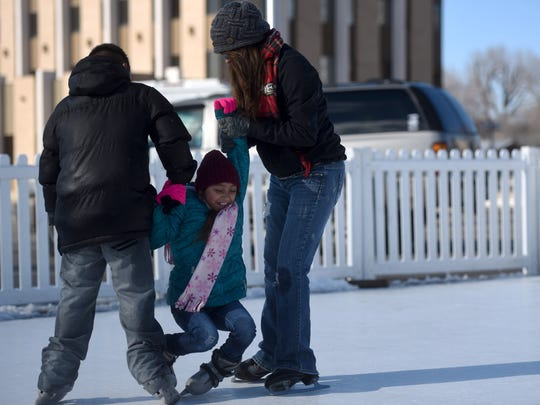 Tacia Westbrook, right, helps her children, 9-year-old Eli Archuleta, and 8-year-old Ciara Archuleta, find their footing Saturday during a visit to the ice skating rink on Arrington Street across from the Farmington Civic Center.