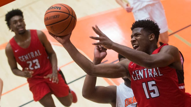 Central's Devone Moss (15) takes a shot while defended by Clinton's Trevon Hill (4) during a game Jan. 27.