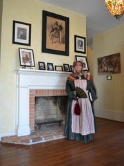 A re-enactor/docent waits on tours to begin through the house.