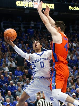 Quade Green, No. 0 of the Kentucky Wildcats, puts up a layup over Egor Koulechov, No. 4 of the Florida Gators, at Rupp Arena on January 20, 2018 in Lexington, Kentucky.