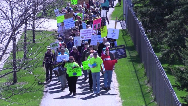 Marchers carry signs and chant as they participate in the Central Wisconsin March for Science on Saturday, April 22, 2017, in downtown Marshfield.