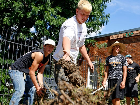 Cody Smith, of Aztec, moves silt and debris from the sidewalk Aug. 27, 2015, at the Aztec Museum after a flood.