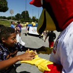 Children offer candy to Louie, the Springfield Cardinals mascot, during the Park Day Reunion parade in Springfield, Mo. on Aug. 1, 2015.