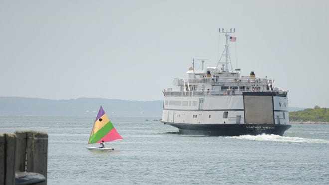 A sunfish boater sails past the Steamship Authority's M/V Martha's Vineyard ferry on its way to the island