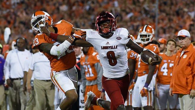 Louisville quarterback Lamar Jackson (8) stiff-arms Clemson safety Van Smith (23).