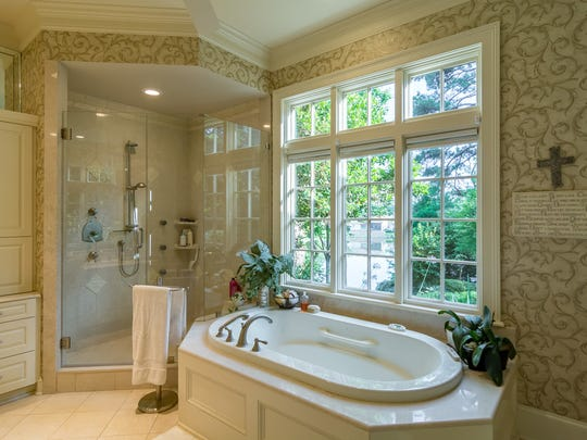 The master bath offers a steam shower and heated stone