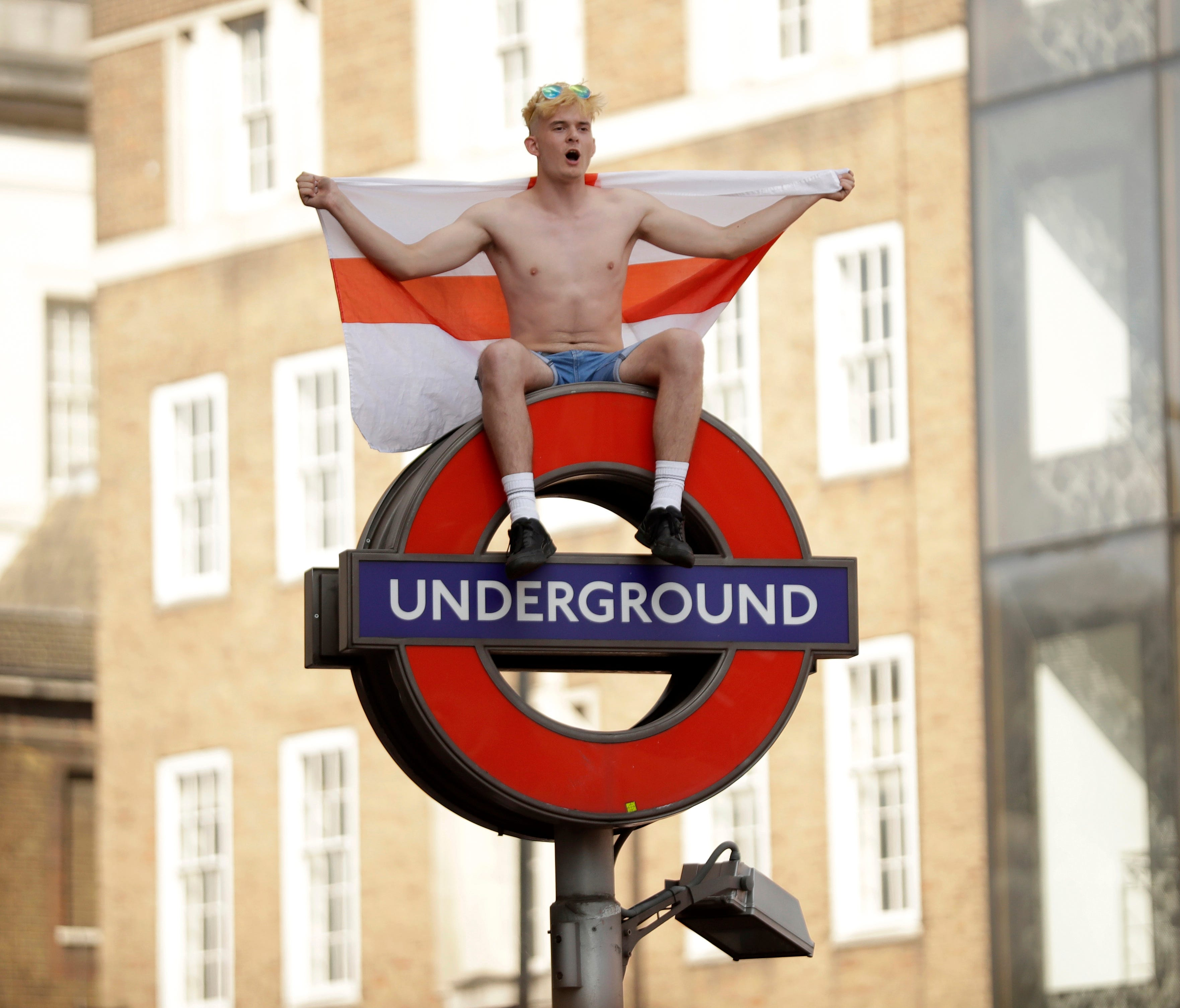 An fan sits with a St George's Cross England flag atop of a London Underground sign.