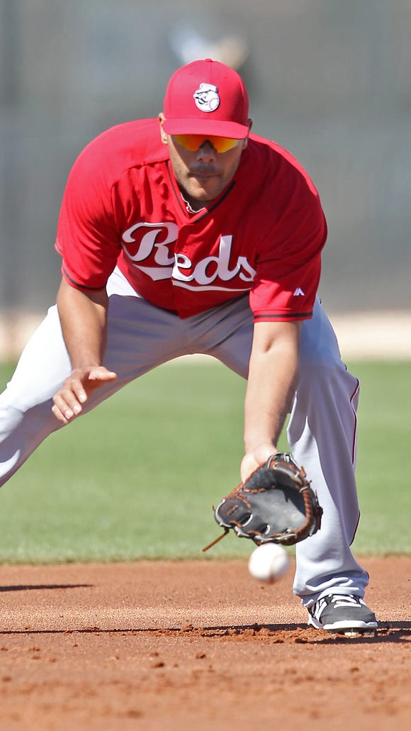 Non-roster invitee infielder Chris Dominguez fields a groundball during drills at spring training in Goodyear, Ariz.