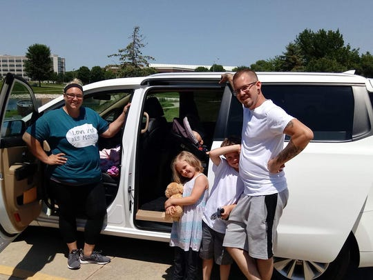 The Rhoades family stands outside of their minivan