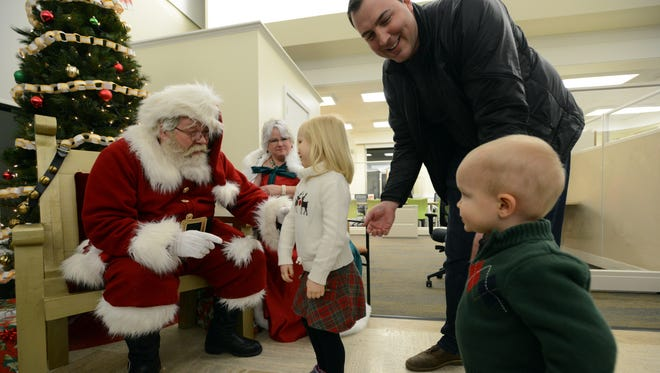 Elaine Haire, 4, walks up to Tim and Ginny Etienne as they portray Santa and Mrs. Claus while her father Lucas Haire tries to talk Grant Haire 1, into going to the Etienne's Friday night, Dec. 1, 2017, in Canal Winchester.