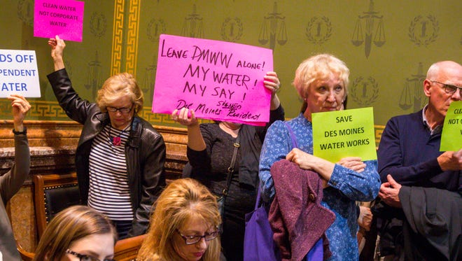 Residents hold signs during public hearing Monday at the Capitol on legislation that would dismantle independent water utilities.