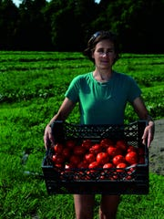 Julia Wycall of Greenbranch Farm holds a crate of red slicers. The farm has been a staple at area farmers markets for eight years.