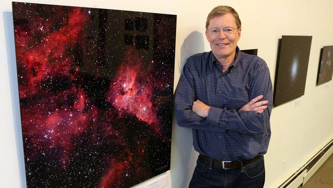 "Scott Nammacher stands next to one of his photographs that are on exhibit at the Pound Ridge Library. Titled ""Treasures of the Northern and Southern Skies,"" the show runs through July 3."