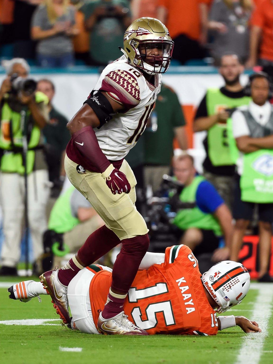 Miami Hurricanes quarterback Brad Kaaya (15) is sacked by Florida State Seminoles linebacker Jacob Pugh (16) during the first half against at Hard Rock Stadium. FSU had three sacks against Miami.