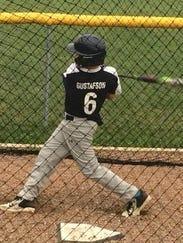 Eli Gustafson follows through on a swing in the batting