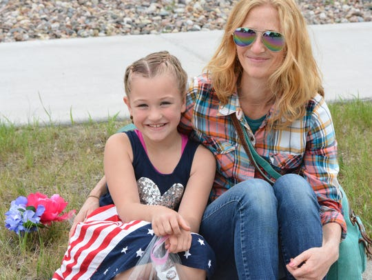Seated at the curb, Taylor and Stacey Baumann enjoy
