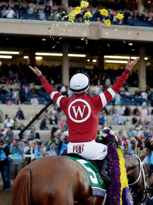 Florent Geroux celebrates after riding Gun Runner to victory in the Classic during the Breeders' Cup horse races, Saturday, Nov. 4, 2017, at Del Mar Thoroughbred Club in Del Mar, Calif. (AP Photo/Gregory Bull)