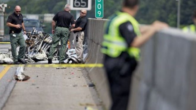 Investigators look at the wreckage of a plane that crashed on Interstate 285 outside Atlanta on Friday. The pilot, Greg Byrd of Asheville, along with two of his sons, Christopher and Phillip, and Christopher's fiancee Jackie Kulzer, died in the crash.