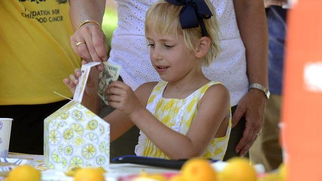 Carolyn Hendrix, 6, handles the money at her lemonade stand g that raised money to help fight childhood cancer Sunday at Trinity Presbyterian Church. Carolyn has been cancer free for a year.
