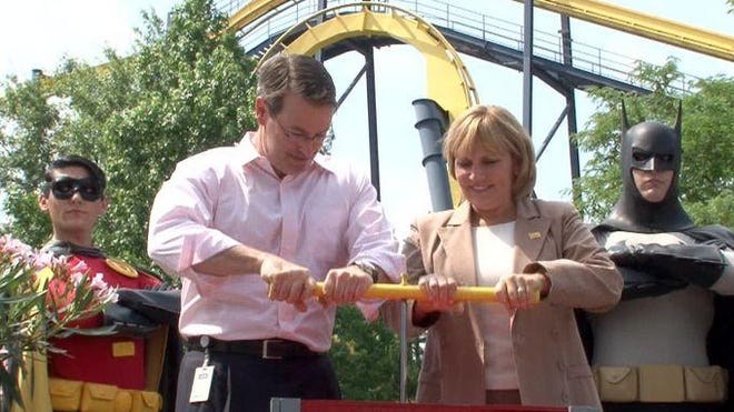 Six Flags Great Adventure president Jim Fitzgerald and New Jersey Lieutenant Governor Kim Guadagno push a plunger to ceremonially open the Batman ride at the Jackson Township, NJ, park Tuesday, July 7, 2015. For a limited time, the chair lift-style train is flipped 180 degrees on the track.