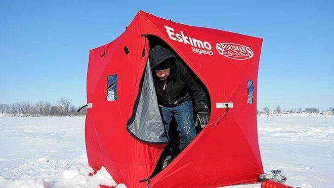 Bret Wynja, of Sioux Falls, gets set up while ice fishing Friday, Jan. 22, 2016, on Wall Lake west of Sioux Falls.