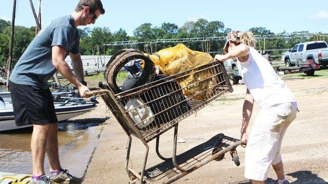 Bryce Hoggatt and Elizabeth Allstaedt lift a grocery cart filled with garbage they fished out of the Ouachita River out of a boat at the Forsythe Boat Launch during the Ouachita River Water Sweep on Sept. 10, 2016.