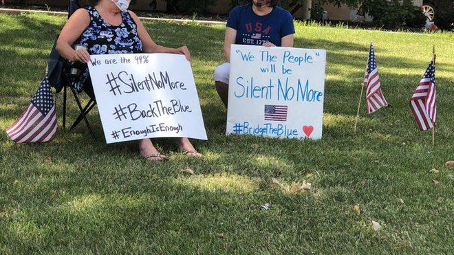 Two women displayed signs while taking part in a rally held Saturday in front of Topeka's City Hall to show support for law enforcement.
