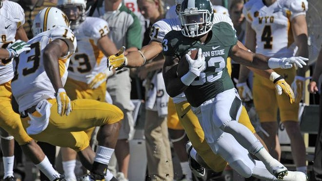 Jeremy Langford (33) reverses and confuses the Cowboys on his way to a first quarter first down as MSU hosts Wyoming Saturday at Spartan Stadium in East Lansing. Lanford finished with 137 yards on 16 carries.