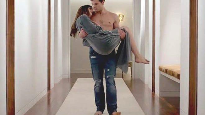 Christian Grey (Jamie Dornan) whisks Anastasia Steele (Dakota Johnson) to the Red Room for a night of passion.