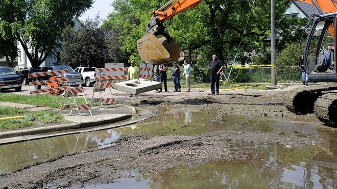 Construction crews work to open the man hole at Cedar Street and 2nd Street in Canton, S.D., Tuesday, June 17, 2014.