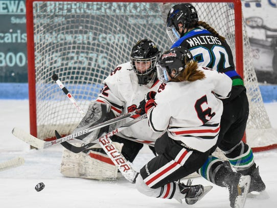The puck skips in front of St. Cloud Icebreakers goaltender