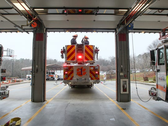 Courtney Brown, right, and Lt. Stephen Teske get ready to try out the 100-foot ladder on the truck at the Clemson University fire department station.