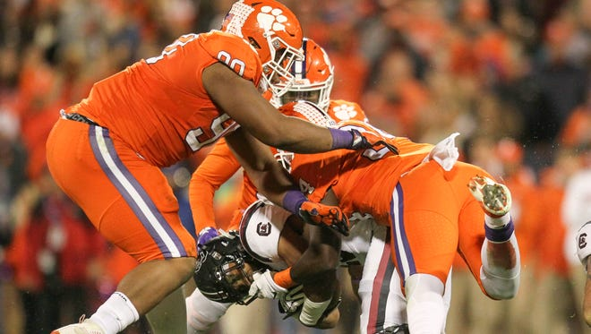 Clemson defensive lineman Dexter Lawrence (90) and linebacker Kendall Joseph (34) tackle South Carolina freshman running back A.J. Turner (25) during the second quarter on Saturday at Memorial Stadium in Clemson.