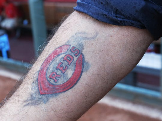 Actor Charlie Sheen and guest analyst on ESPN's Baseball Tonight showed off his Cincinnati Reds tattoo while hanging out at batting practice at Great American Ball Park prior to their game against the St. Louis Cardinals.