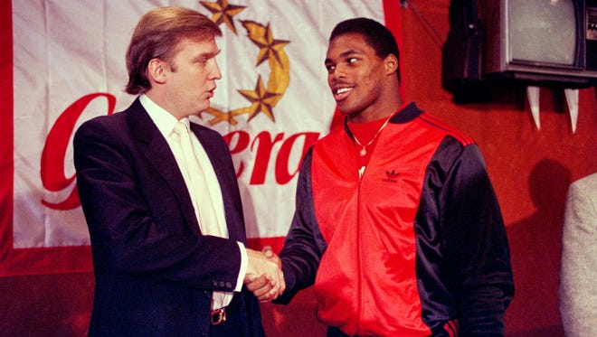 In this March 8, 1984, file photo, Donald Trump shakes hands with Herschel Walker in New York after agreement on a 4-year contract with the New Jersey Generals USFL football team. The New Jersey Generals have been largely forgotten, but Trump's ownership of the team was formative in his evolution as a public figure and peerless self-publicist. With money and swagger, he led a shaky and relatively low-budget spring football league, the USFL, into a showdown with the NFL.