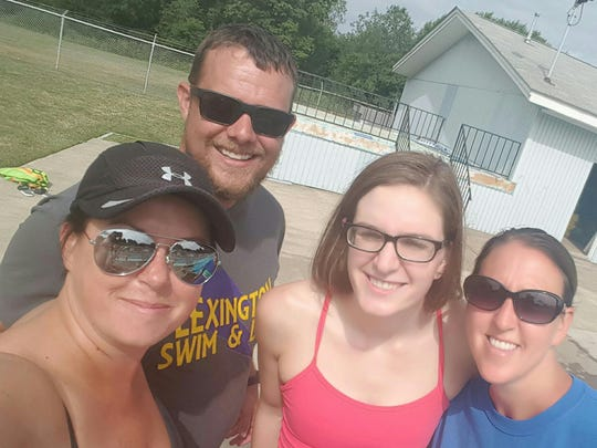 Hannah Stevens (second from right) received a nice reception Wednesday at Walnut Hills Swim Club from adults and kids, including left to right, Libby Nickoli and her high school and summer coaches Brock Spurling and Melisa Stone-Watters.
