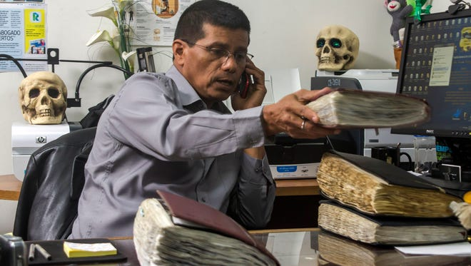 In this Oct. 6, 2014, photo, criminologist Israel Ticas talks on the phone as he stacks his field notebooks, at his office in San Salvador, El Salvador.