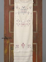 This hand towel embroidered by Susanna Groff Steinweg (1794-1879) hangs on a white pine and tulip poplar door made for displaying the handiwork. This towel would never have been used. It's for decoration only.