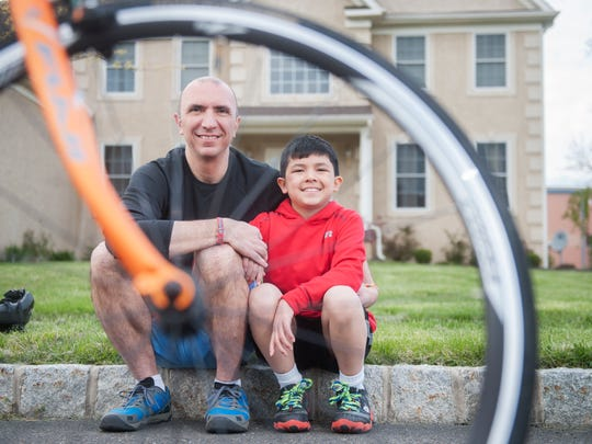 Alec Kazandjian, 11, who was diagnosed with acute lymphoblastic leukemia when he was 9, sits with his father, Hakop Kazandjian, in front of their Mount Laurel home. They're training to ride in the 43rd annual American Cancer Society's Bike-a-thon, which begins in Philadelphia and ends in Atlantic City.